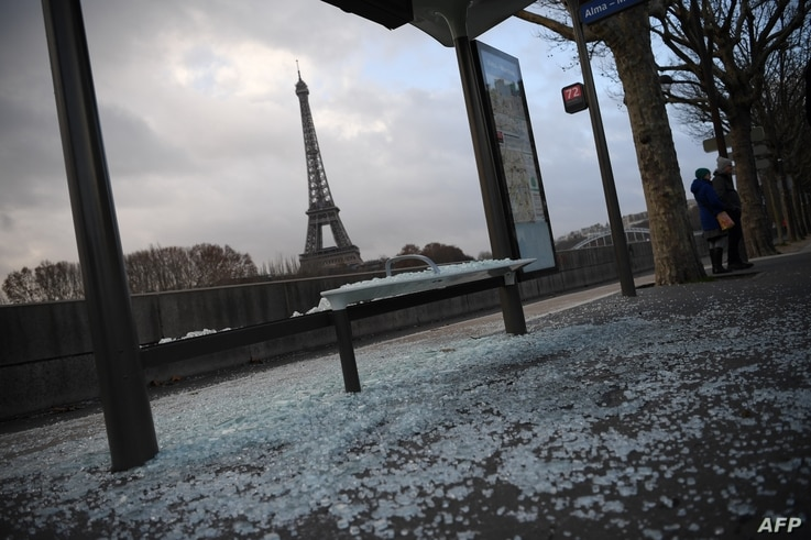 "A picture taken in Paris, Dec. 9, 2018, shows a broken bus stop and (background) the Eiffel tower a day after a ""yellow vest"" protests as part of a fourth weekend of nationwide protests."