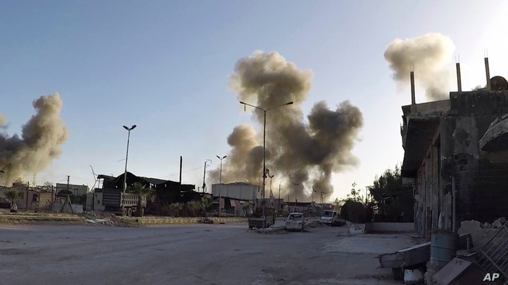 This photo released by the Syrian Civil Defense White Helmets, which has been authenticated based on its contents and other AP reporting, shows smoke rising after Syrian government airstrikes hit in the town of Douma, in the eastern Ghouta region eas