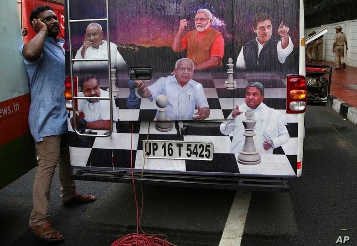 A journalist talks on his mobile phone next to an outdoor broadcasting vehicle plastered with portraits of Indian political leaders, in Bangalore, India, May 15, 2018.