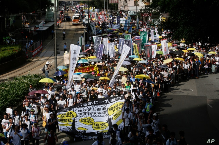Pro-democracy protesters march during an annual protest marking Hong Kong's handover from British to Chinese rule in 1997 in Hong Kong, Wednesday, July 1, 2015. Thousands of Hong Kongers in crowds noticeably smaller than previous years took to the st...