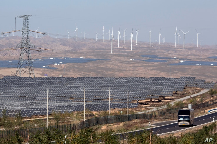 FILE - In this file photo taken Oct. 10, 2015, a bus moves past by solar power and wind power farms in northwestern China's Ningxia Hui  region.