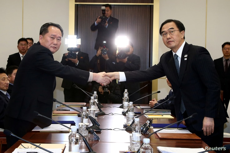 Head of the North Korean delegation, Ri Son Gwon shakes hands with South Korean counterpart Cho Myoung-gyon as they exchange documents after their meeting at the truce village of Panmunjom in the demilitarized zone separating the two Koreas, South Ko...