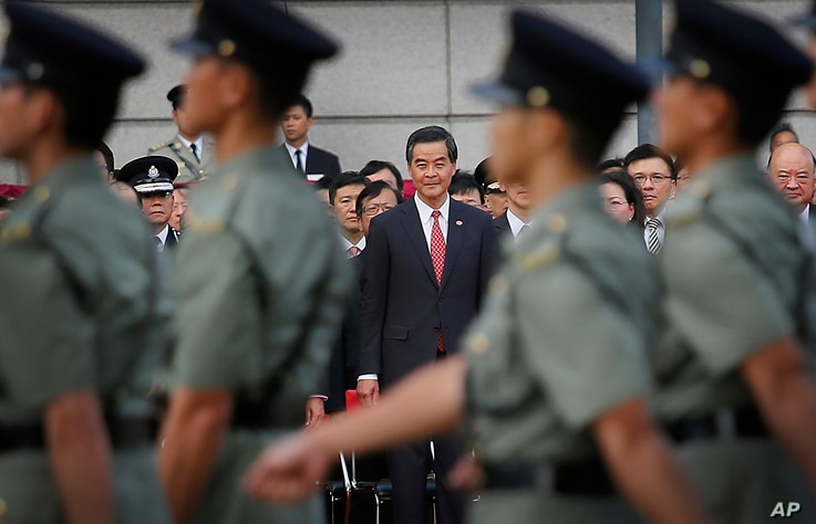 Hong Kong's Chief Executive Leung Chun-ying, center, watches as military personnel march during a flag-raising ceremony as thousands of protesters watching from behind police barricades yelled at him to step down in Hong Kong, Oct. 1, 2014.