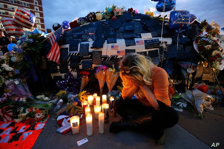 Tasha Lomoglio, of Dallas, cries after lighting candles at a makeshift memorial in honor of the slain Dallas police officers in front of police headquarters in Dallas, Texas, July 9, 2016.