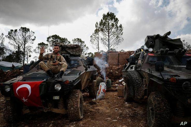 Syria TurkeyA Turkish soldier waves sitting atop a military vehicle on at Bursayah Hill, Afrin region, March 3, 2018, during a Turkish government-organized media tour into northern Syria.