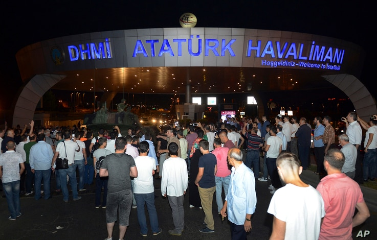 People stand in front of a tank parked in the entrance to Istanbul's Ataturk airport, July 16, 2016. Members of Turkey's armed forces said they had taken control of the country, but Turkish officials said the coup attempt had been repelled early Satu...