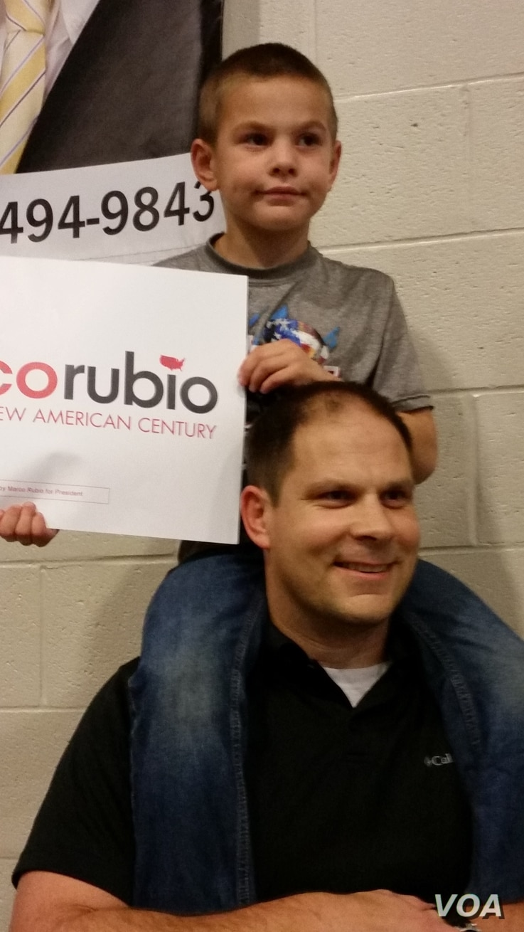 """Mark Jones of Summerville, whose son Rig is perched on his shoulders, holds a Marco Rubio sign at a South Carolina rally Feb. 19, 2016. Even after the rally, Jones says he's still undecided, though """"90 percent"""" for Rubio. (C. Guensburg/VOA)"""