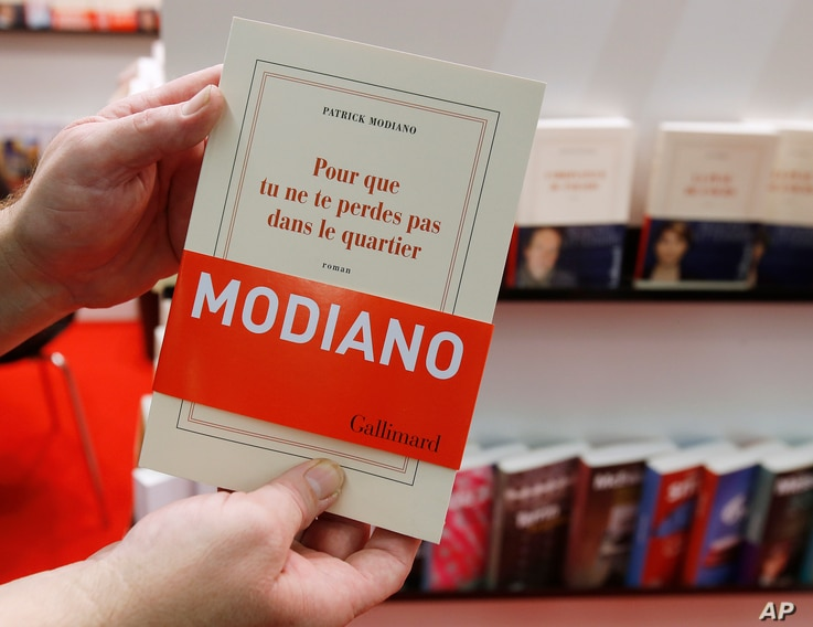 A man holds a book of French author Patrick Modiano at the Book Fair in Frankfurt, Germany, Oct. 9, 2014.