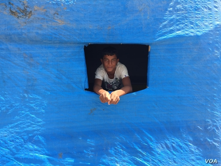A displaced Sunni teenager looks out of a window cut into plastic blue sheeting covering his new home in the Baharka camp on the outskirts of Irbil, in the Kurdistan region of Iraq, Aug 5, 2015 (VOA photo - Sharon Behn).