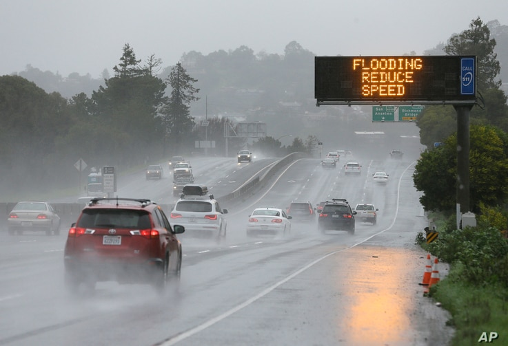 A sign warns motorists of flooding on northbound Highway 101, Feb. 20, 2017, in Corte Madera, Calif.