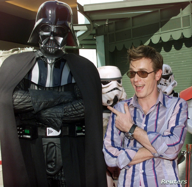 """Scottish actor Ewan McGregor, who portrayed Obi-Wan Kenobi in """"Star Wars Episode II Attack of the Clones,"""" poses with Star Wars character Darth Vader and Storm Troopers in background at the Los Angeles charity premiere of the film, May 12, 2002, in H..."""