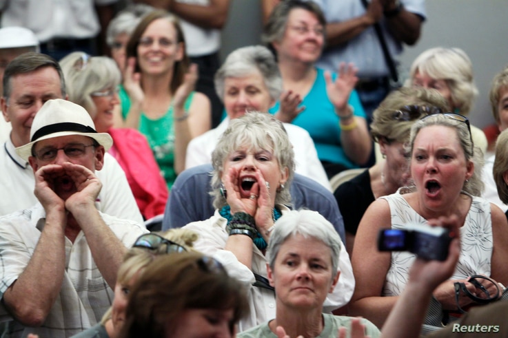 FILE - People shout at a town hall meeting on health care reform hosted by Rep. Mike Coffman, R-Colo., in Littleton, Colorado, Aug. 12, 2009.
