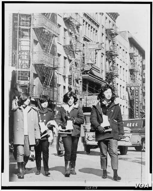 Four Chinese American girls carrying ice skates in Chinatown, New York City