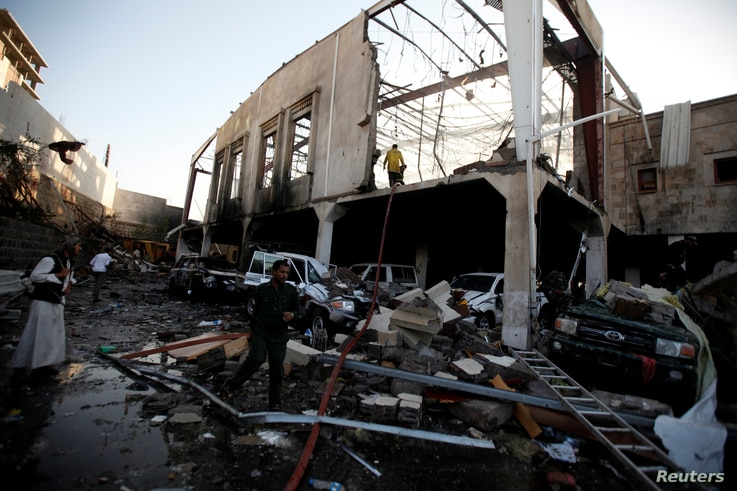 People stand at the site of an airstrike on a hall where a wake for the father of Jalal al-Ruweishan, interior minister in the Houthi-dominated Yemeni government, was being held, in Sana'a, Yemen, Oct. 8, 2016. Witnesses attributed the airstrike to S