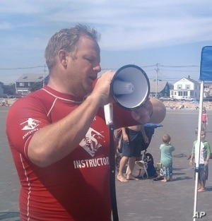 AmpSurf founder Dana Cummings commands the beach with his megaphone as he welcomes participants to a surfing class in Maine.