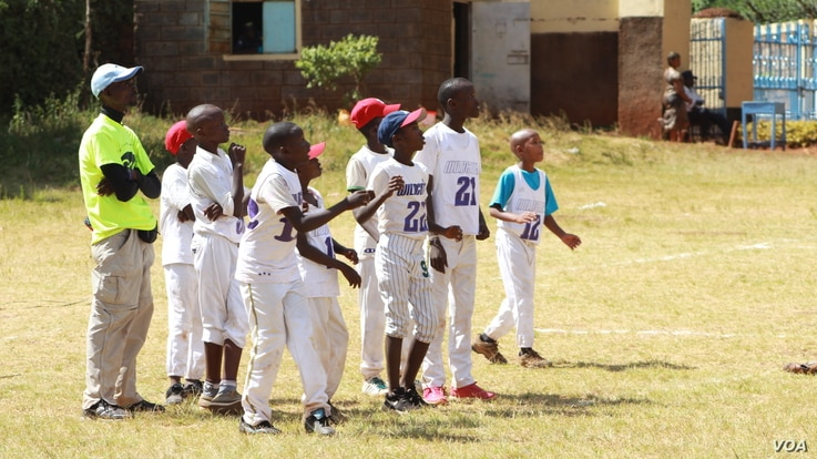Coach Chapman Owino and some of his Kilimanjaro All Stars watch the action. (L. Ruvaga/VOA)