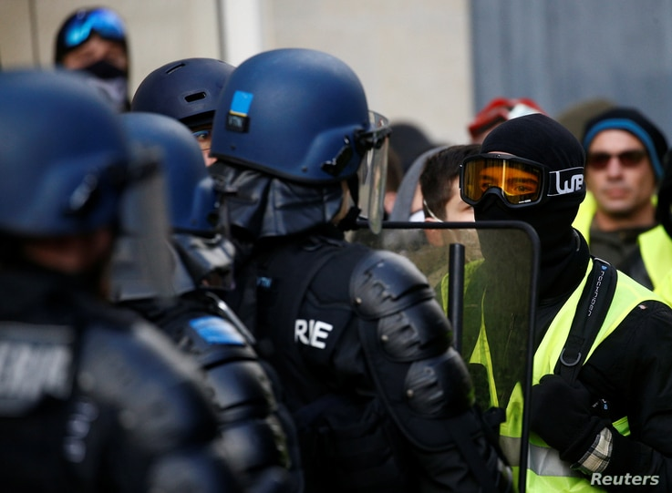 "Protesters wearing yellow vests face riot police during a demonstration of the ""yellow vest"" movement in Angers, France, Jan. 19, 2019."