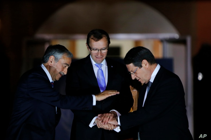 FILE - Cyprus' president Nicos Anastasiades, right, Turkish Cypriot leader Mustafa Akinci, left, and United Nations envoy Espen Barth Eide shake hands after a dinner at the Ledra Palace Hotel inside the U.N.-controlled buffer zone that divides the Cy...