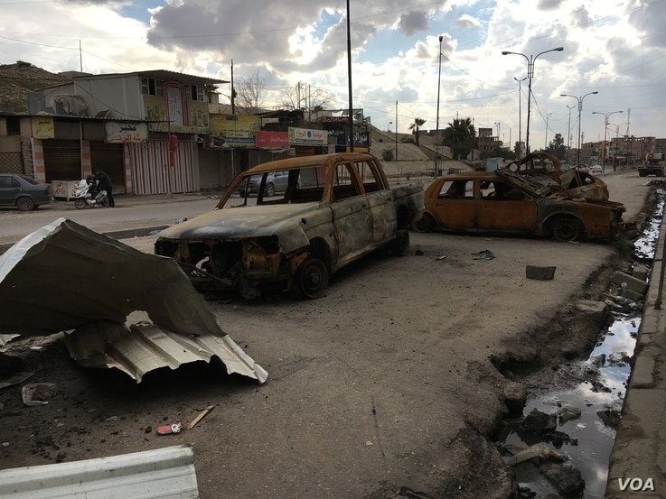 Burned vehicles in front of Nabi Yunis Shrine  on a public road in east of Mosul, Iraq.