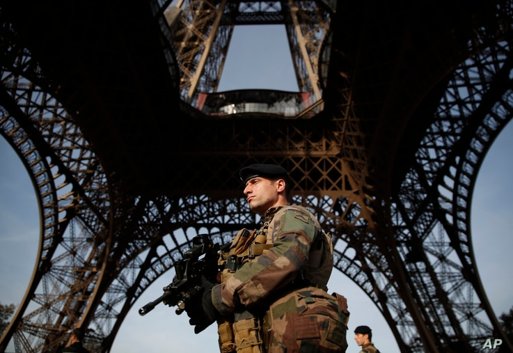 A soldier stands guard under the Eiffel Tower in Paris, France, Nov. 1, 2017 .