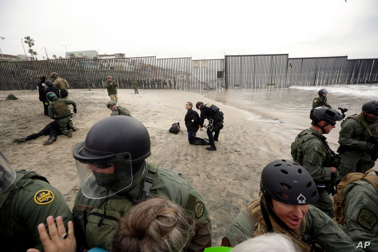 A woman is detained during a protest in San Diego, near the border with Tijuana, Mexico, Dec. 10, 2018.