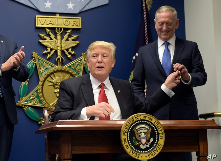 FILE - President Donald Trump (L) hands Defense Secretary Jim Mattis a pen after signing an executive action on rebuilding the U.S. military, during an event at the Pentagon, near Washington, Jan. 27, 2017.