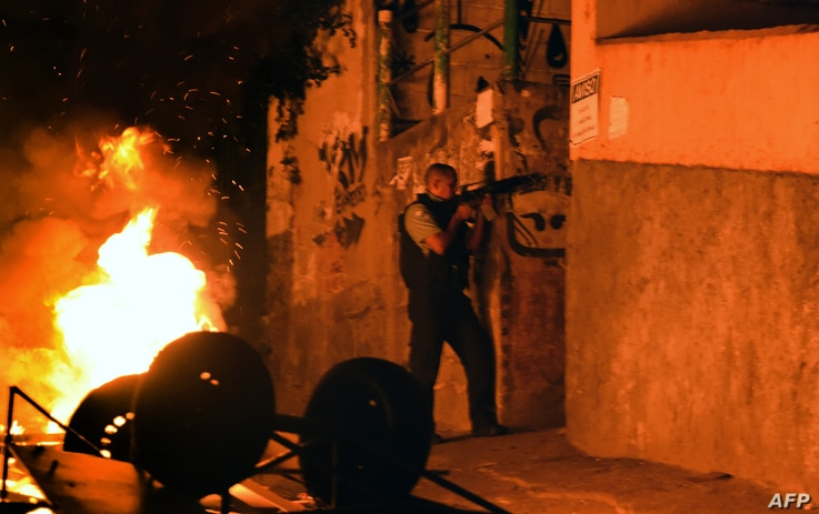 A military policemen stands in position during a violent protest in a favela next to Copacabana, Rio de Janeiro, April 22, 2014.