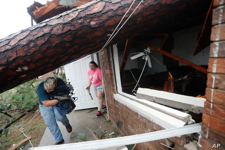 Megan Williams, left, and roommate Kaylee O'Brian take belongings from their destroyed home after several trees fell on the house during Hurricane Michael in Panama City, Fla., Oct. 10, 2018.