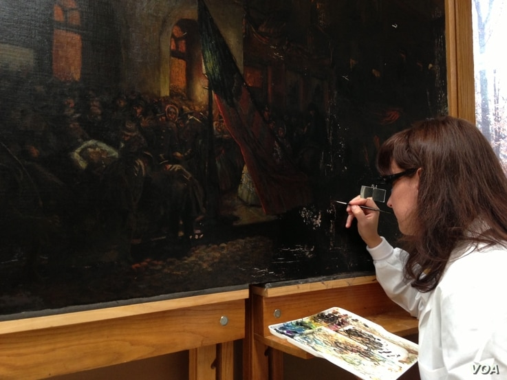 """Marta Brassfield, one of the Senior Painting Conservators with Olin Conservation, Inc., uses a fine brush to inpaint damaged areas of """"Borne by Loving Hands,"""" a painting by German artist Carl Bersch that captures the aftermath of President Abraha..."""