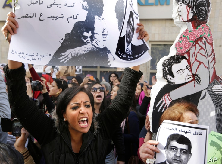 """An Egyptian protester chants anti interior ministry slogans as she holds a poster of Shaimaa el-Sabagh, an activist who was shot dead at a small peaceful protest last Saturday, with Arabic that reads, """" how many martyrs remaining for victory,"""" during"""