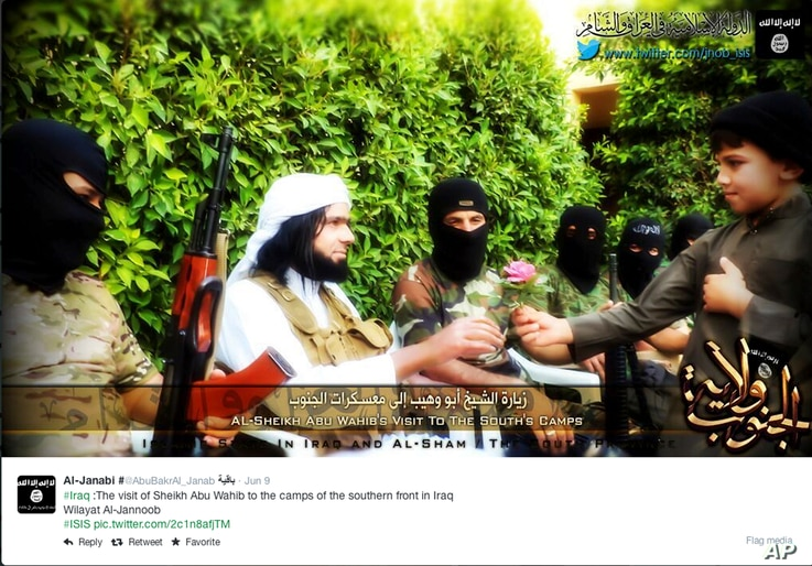 FILE - This screen grab from an Islamic State group affiliated Twitter account, taken Sunday, Sept. 20, 2014, purports to show senior military commander Abu Wahib handing a flower to a child while visiting southern Iraq, as part of the group's broad