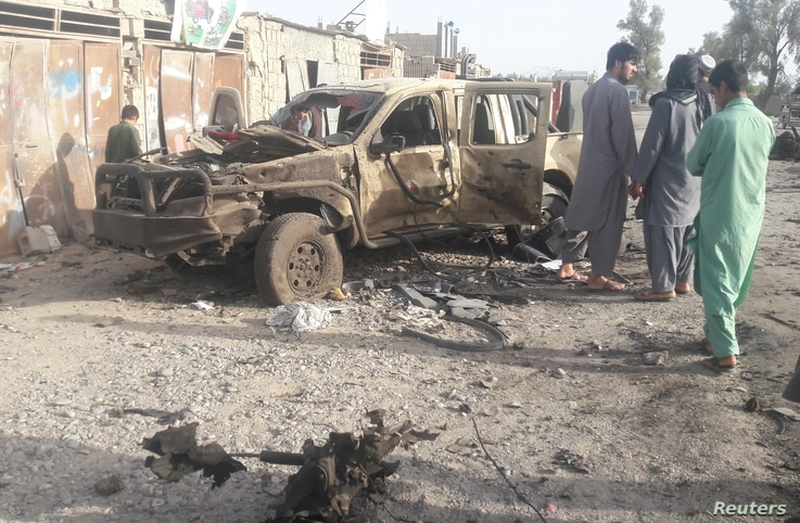 Residents look at an Army vehicle which was damaged during battle between Afghan security forces and Taliban in Farah province, Afghanistan, May 16, 2018.