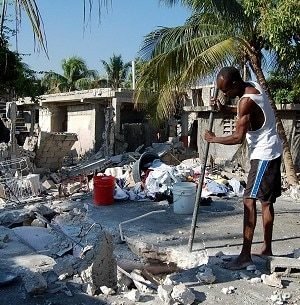 A man in Carrefour, Haiti, near the quake's epicenter, attempts to dig out whatever possessions he can salvage from his destroyed home, 25 Jan 2010