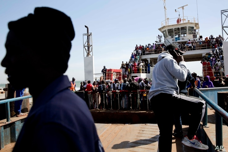 A ferry carrying people who fled Gambia arrives at the port in Banjul, Gambia, Jan. 22, 2017, one day after Gambia's defeated leader Yahya Jammeh left the country.