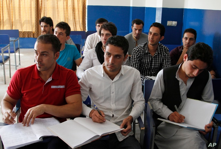 FILE - Afghan students take notes in a business administration class at Kardan University in Kabul, Afghanistan, Sept. 10, 2013. By targeting the educated militants hope to increase the number of uneducated youth – a prime demographic in Afghanista...