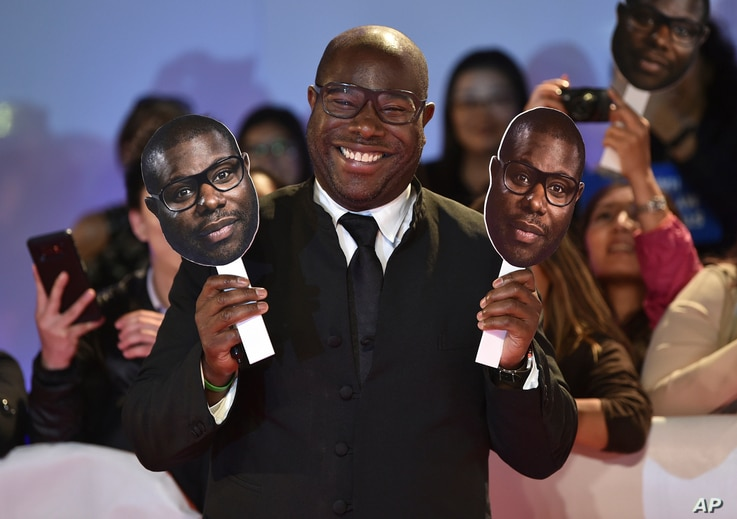 """Director Steve McQueen poses with paper cutouts of his face as he attends the premiere for """"Widows"""" on day 3 of the Toronto International Film Festival at Roy Thomson Hall, Sept. 8, 2018, in Toronto."""