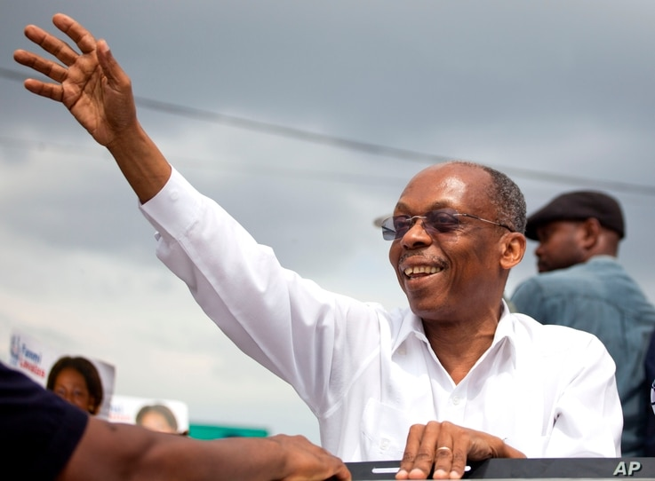 Haiti's former President Jean-Bertrand Aristide waves to supporters as he campaigns with presidential candidate Maryse Narcisse of the Fanmi Lavalas political party, in Petion-Ville, Haiti, Aug. 29, 2016.