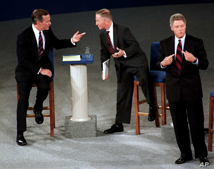 This October 15, 1992 photo shows then President George H. W. Bush, talking with independent candidate Ross Perot as Democratic candidate Bill Clinton stands aside at the end of their second presidential debate in Richmond, Virginia.