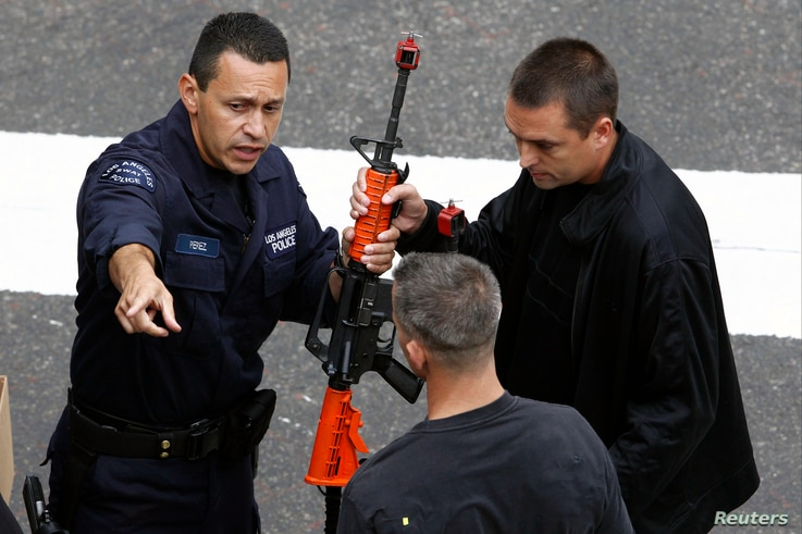 FILE - Police officers pretending to be terrorists receive training weapons during a live counterterrorism demonstration for the 2013 National Homeland Security Conference, in downtown Los Angeles, June 6, 2013.