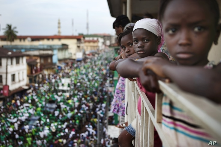 Girls watch a rally for Sierra Leone opposition presidential candidate Julius Maada Bio from their terrace in downtown Freetown, November 15, 2012.