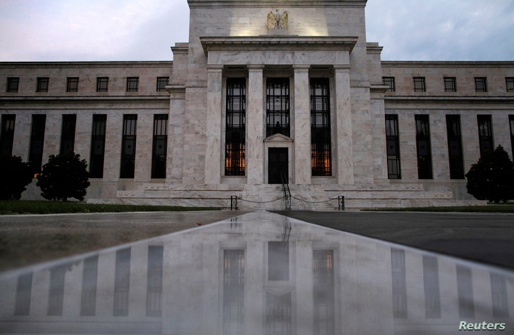 The facade of the U.S. Federal Reserve building is reflected on wet marble during the early morning hours in Washington, July 31, 2013.