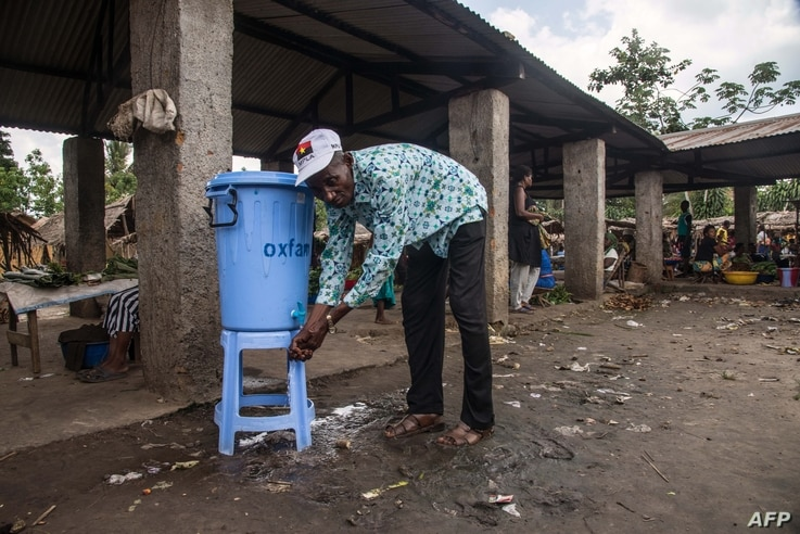 """A man washes his hands with water from a dispenser containing water mixed with disinfectant at the Congo Air Market on the airport road in the east of Mbandaka, DRC, May 23, 2018. An Ebola outbreak in the Democratic Republic of Congo has a clear """"po..."""