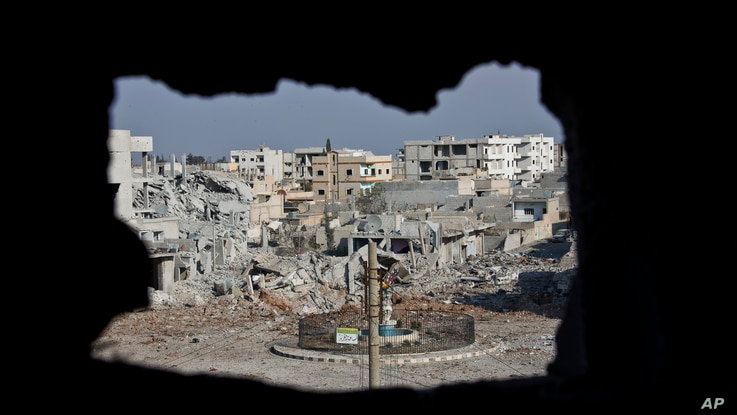 FILE - An area controlled by the Islamic State group, past the Qada Azadi roundabout, foreground, in Kobani, Syria, Nov. 20, 2014.