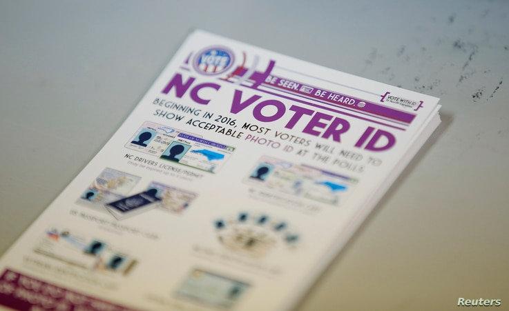 "A pile of government pamphlets explaining North Carolina's controversial ""Voter ID"" law sits on table at a polling station."