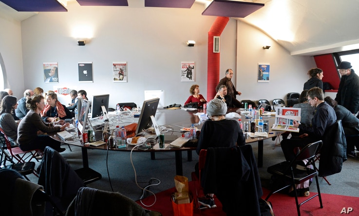 FILE - Editorial staff of the French satirical magazine Charlie Hebdo share the offices of the French newspaper Liberation, in Paris, Jan. 9, 2015.