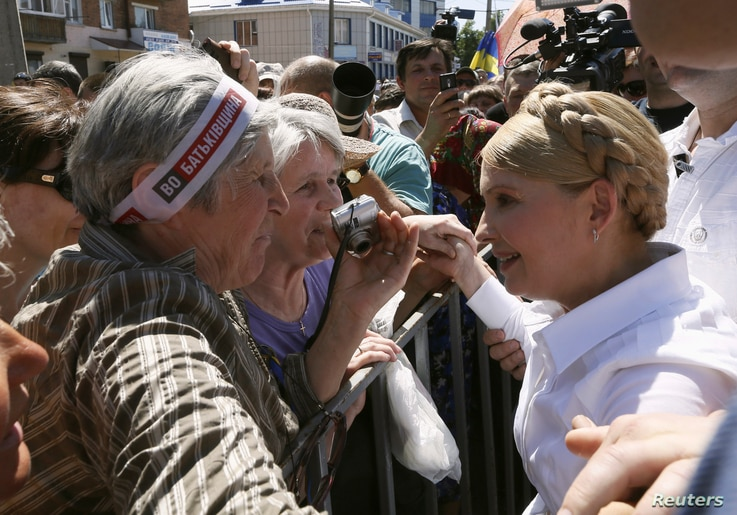 Former Ukrainian prime minister and current presidential candidate Yulia Tymoshenko (R) meets supporters during her election campaign in the city of Konotop May 21, 2014. Campaigning for Ukraine's presidential election, Tymoshenko says she alone can ...