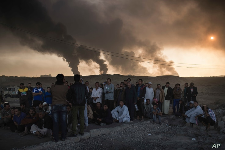 Men are held by Iraqi national security agents, to be interrogated at a checkpoint, as oil fields burn in Qayara, south of Mosul, Iraq, Nov. 5, 2016. Islamic State fighters are launching counterattacks in the thin strip of territory Iraqi special for...