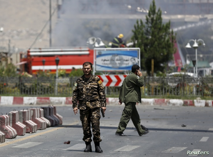 An Afghan security personnel holds his gun as he keeps watch near the site of a car bomb blast at the entrance gate to the Kabul airport in Afghanistan, August 10, 2015.
