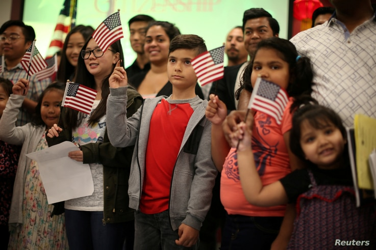 Children say the pledge of allegiance during a ceremony to present citizenship certificates to young people who earned citizenship through their parents, in Los Angeles, California, May 31, 2017.