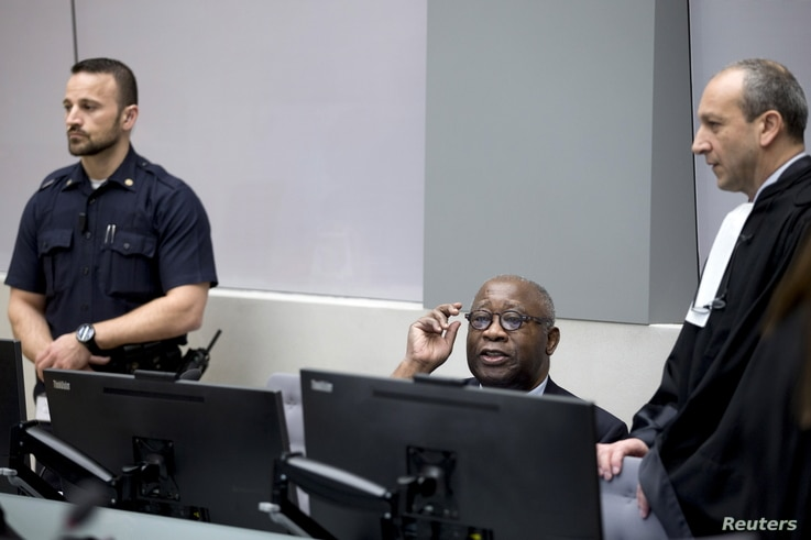FILE - Former Ivory Coast President Laurent Gbagbo, center,  and his lawyer Emmanuel Altit, right, wait for the start of the trial at the International Criminal Court in The Hague, Netherlands, Jan. 28, 2016.